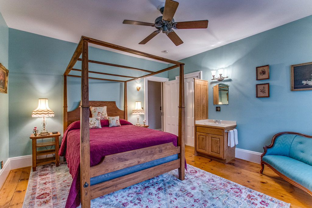 teal room with red bedspread view 2