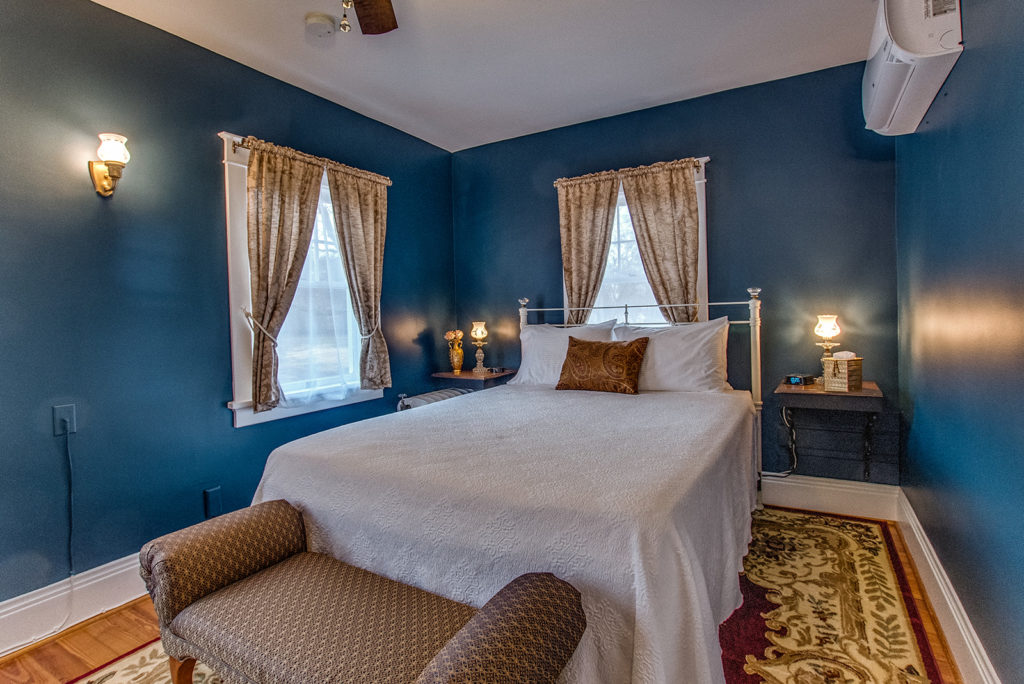 blue room with white bed spread view 2
